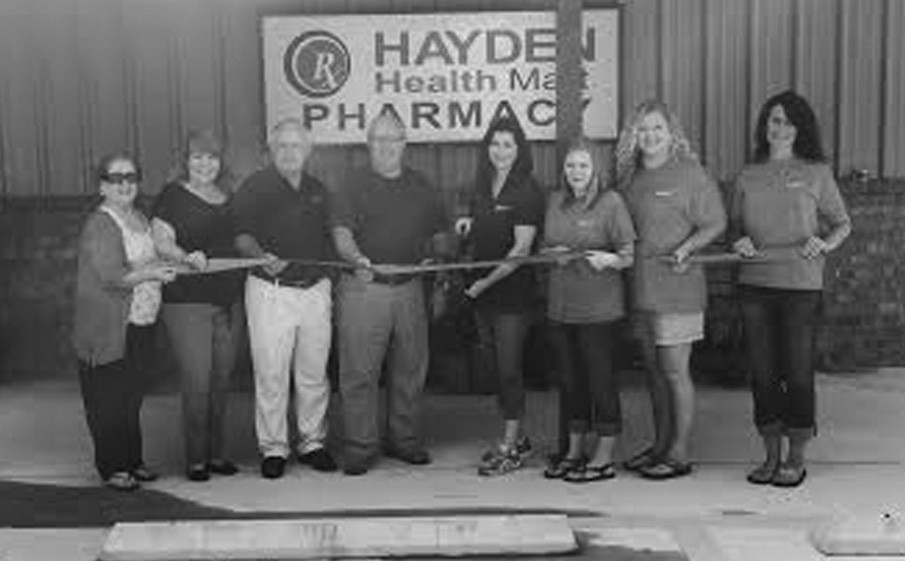Hayden Health Mart Pharmacy held its grand opening Saturday at its new location on Ala 160, across from Hayden Primary and Hayden Elementary schools. From left above: Delores Fort, West Blount Chamber of Commerce; Kim Calvert, West Blount Chamber; Hayden Mayor Larry Armstrong; Greg Reid, West Blount Chamber; Hayden Health Mart Pharmacy owner Jennifer Metcalf; pharmacy employees Cacee Jewell and Angela Bencko, and store manager Kim James. Metcalf said the store was moved in February from its old location off Ala 160 to provide more convenience, store space, and parking to customers. The new store provides more space for gift items, more over-the-counter drug products, and a wider variety of drugstore consumer items generally. The new location features a drive-through for prescriptions, and delivery service is being expanded, Metcalf said. Also being expanded is the range of immunizations available at the store, limited in the past to flu shots. She noted the store continues under her ownership, adding she has been a part of the Hayden community for more than 20 years. – Ron Gholson