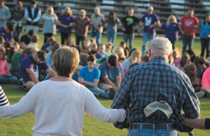 Susan Moore residents of all ages gather on the football field to pray for community healing.