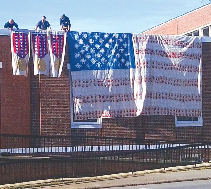 This past weekend, a handmade American flag and eight banners were hung from the Blount County Board of Education roof during the Veterans Day parade. The flag was made last year during Hayden High School's Veterans Day program, according to Hayden High counselor Karron Standridge. Each part of the flag was made with faculty, staff, and student hand prints. The red and white hand prints from the students, and the blue hand prints from the faculty and staff. In addition, this year, the school made eight banners (only three of those are pictured) with each star representing a Blount County resident who lost their life in war. – Nicole Singleton