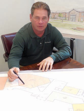 Oneonta city manager Ed Lowe reviews plans for the proposed new city building at the current site of the Oneonta Public Library.