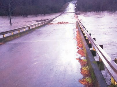 Photo of County Road 51 bridge spanning Mulberry Fork and connecting Blount and Cullman counties northwest of Blountsville. This unusual photo was taken by local resident Beau Larue during the night of rising waters, illuminated at the moment of a lightning strike.