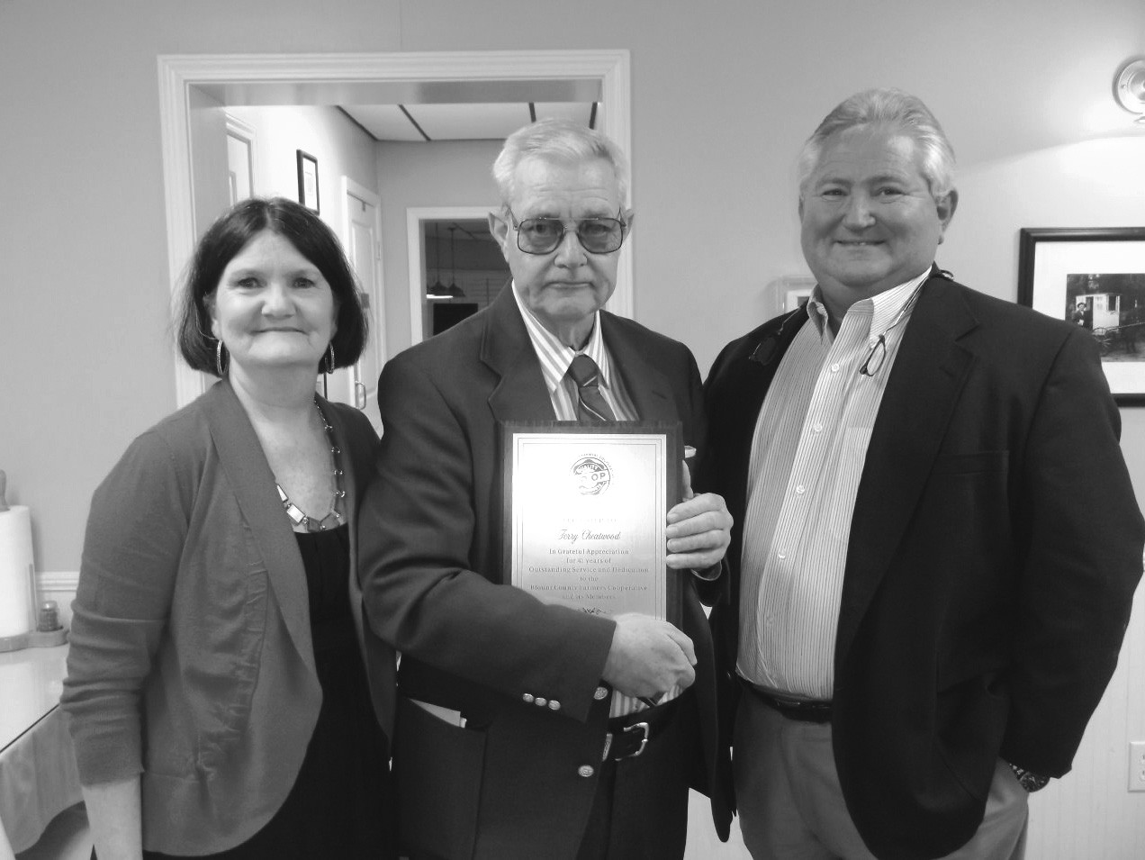 Terry Cheatwood (center) with wife, Elaine, accepts a plaque from Jeff Hallmark, president of the Blount County Co-Op, for 41 years of outstanding service and dedication.