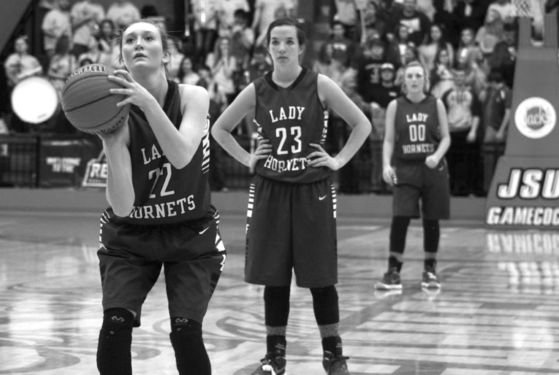 Kimberly Horton shoots a free throw as teammates Madison Cater and Jaime Gail Hudson look on.