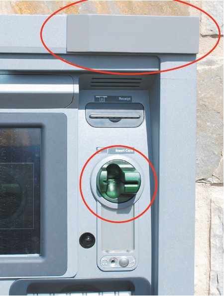 The gray, rectangular object ovaled in red at the top right of the photo is the device that records the customer as they key in a PIN. The green plastic piece circled in red is the actual skimmer that collects the card number from the magnetic strip.
