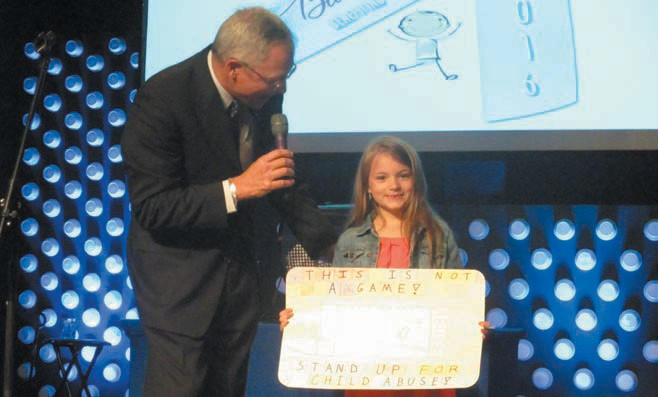 Addison Self (with Jim Ed Clayton) displays her winning poster during last week's Blue Ribbon Banquet.