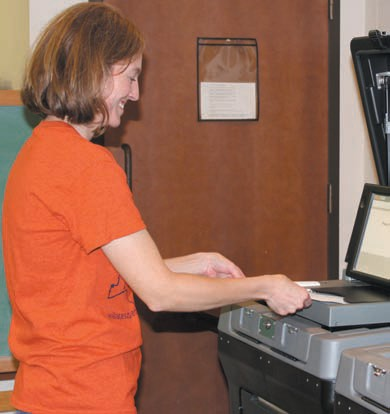 Tanya Alexander slides her test ballot into the electronic vote counter.