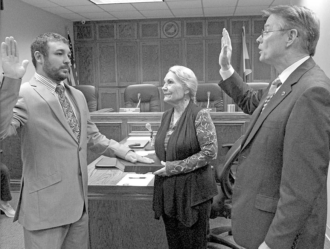 From left, new District 4 Commissioner Nick Washburn is sworn in by Commission Chairman Chris Green as Nick's grandmother, Charlene Story, assists in the ceremony. Washburn thanked his supporters and relatives for attending the event, and thanked the community for their support and for giving him the opportunity to serve.