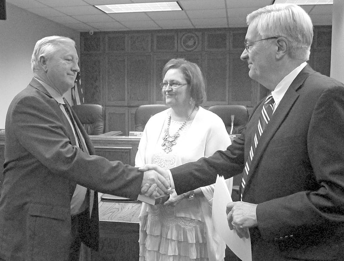 From left, new District 2 Commissioner Mike Painter receives congratulations after swearing in as his wife, Brenda, looks on. Drug court Judge John Dobson administered the oath. Painter spoke briefly after the ceremony, thanking his former teachers and coaches, Dobson, and his father for their influence, promising to work first, for the good of the entire county, and second, in the best interests of District 2, during his term of office.