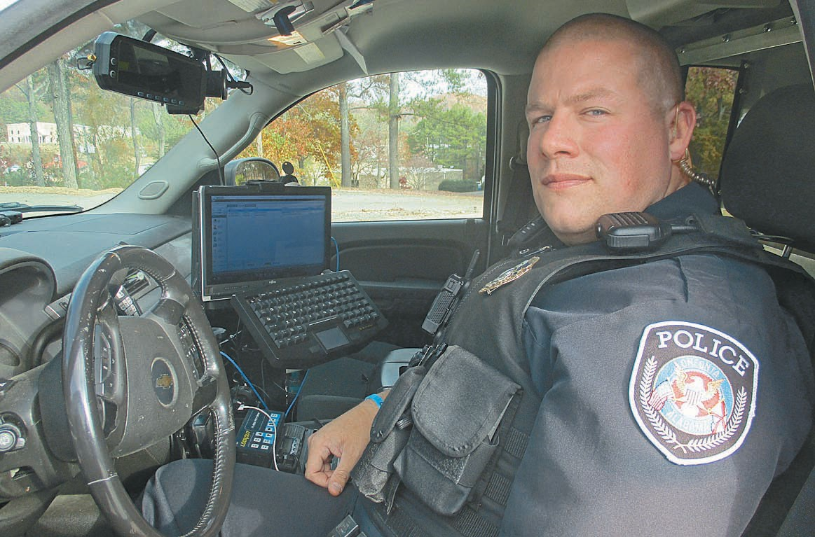 Oneonta patrolman Tommy Herd displays the first responder's mobile component of the computer-aided dispatch system. The laptop on the passenger side of the cruiser basically duplicates and receives dispatch and mapping information from 911.