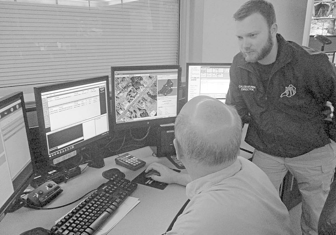 Neal Brooks, left, 911 dispatch supervisor, and Caleb Branch, 911 Center director, demonstrate the computer-aided dispatch system for press and television media.