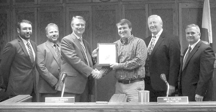 Resigning: Zac Marsh receives framed resolution for four years' hazardous duty as county administrator. Quotable: Commissioner Dean Calvert, after praising Marsh at length for his near-legendary super-savvy computer and mathematical analysis skills concluded with this gem – 'That's where I go to find out my ideas ain't no good!'