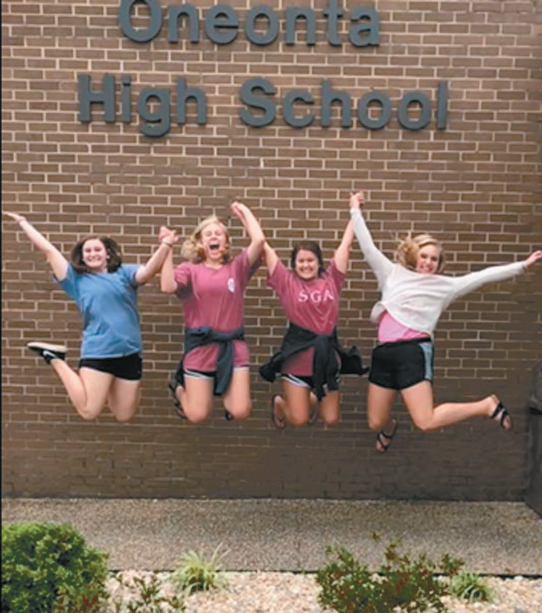 Taylor Claburn, Ashton Boyd, Savannah Tibbet, and Karalise Cook are jumping for joy as they graduate from Oneonta High School.