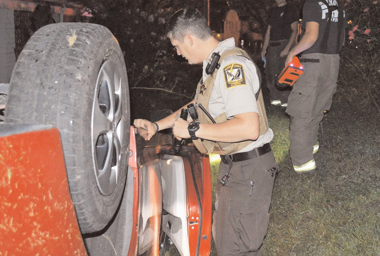 Blount County Sheriff's Deputy Josh Southwell inspects the wrecked vehicle.