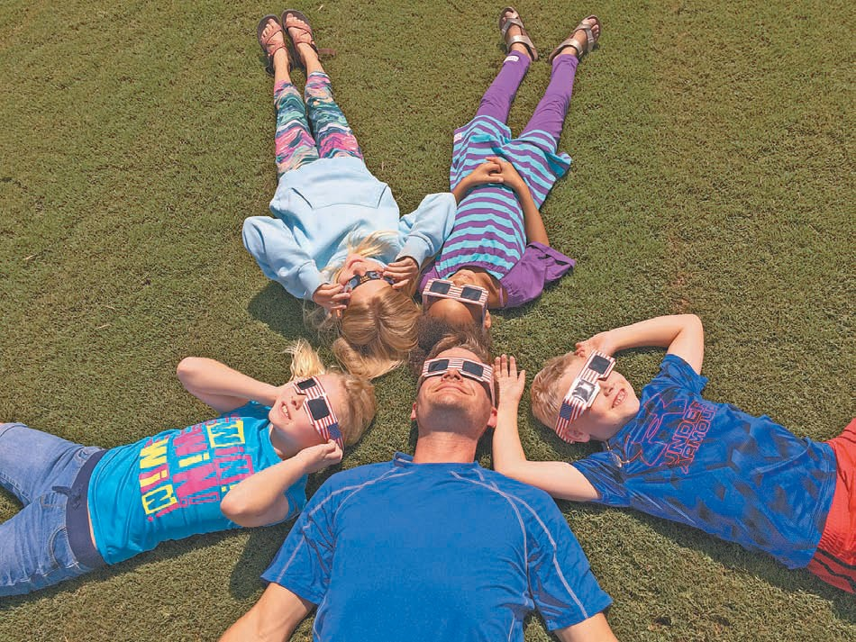 Left: Brett King views the partial eclipse with his children and their classmates at Locust Fork Elementary School. Clockwise from Brett are Ella Brook King, Breanna Boatright, Abby Grace Evans, and Zeth King.